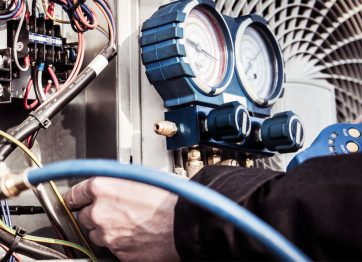 Hands with tools working on an air conditioning unit showing pressure valuves and wiring